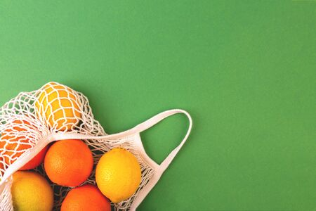 Reusable fruit net bag with oranges and lemons on green background. Zero waste concept. Flat lay, copy space. Archivio Fotografico