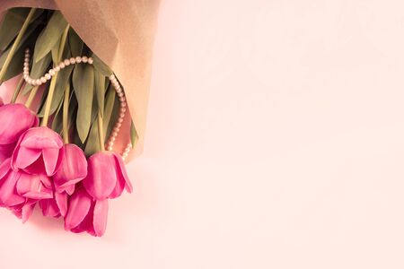 Pink tulips with pearls on a pastel backdrop. Copyspace.Pink tulips with pearls on a pastel backdrop. Copyspace. Archivio Fotografico