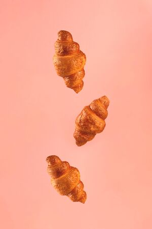 Croissants flying on pink background. Levitation scene.