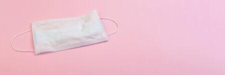 Disposable mask on pink backdrop. Coronavirus outbreak. Medical support equipment.