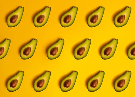 Ripe juicy halved  avocado on a yellow solid background with copy space. Vegan, vegetarian, raw organic food pattern. Eco detox style.