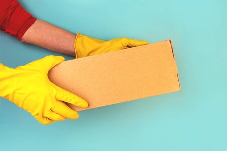 Box with ordered goods in the hands of a courier. Rubber gloves, contactless delivery. Quarantine, self-isolation.