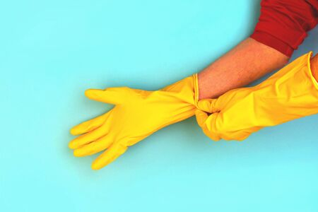 Hands of an elderly man wearing rubber protective gloves. Hygiene House Cleaning.