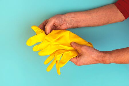 Hands of an elderly tanned man holding yellow rubber protective gloves. Self-isolation, quarantine, domestic housework.