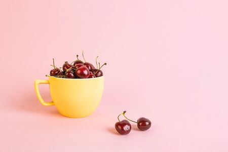 Cherry in a yellow cup on a pink background.