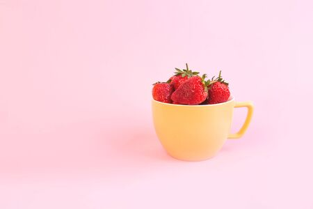 Juicy strawpberry in yellow cup. Stock Photo