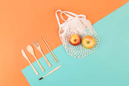 Reusable wooden cutlery and grocery bag. Eco friendly fork, knife, spoon, apple on a mint orange background. Zero waste concept. Copyspace.