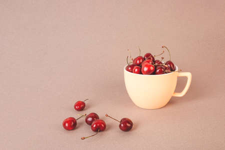 Cherry in a yellow cup on a beige background.