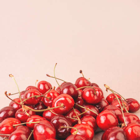 Handful of sweet cherry on a beige background. Copyspace. Stock Photo