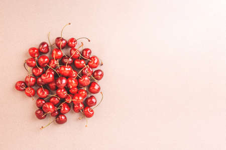 Cherry on a beige background. Copy space.