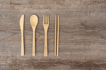 Reusable wooden cutlery. Eco friendly fork, knife, spoon, sticks on an old wooden background. Zero waste concept. Copyspace.