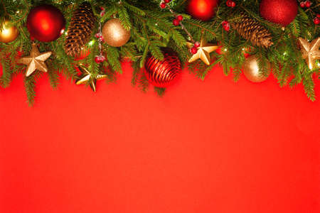 Christmas background with copy space. Festively decorated spruce branches on a red banner. Flat lay style.