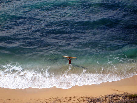 Aerial view of Surfer carrying surfboard into water, Diamond Head Beach, Hawaii photo