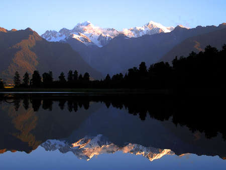 Mount Cook and Mount Tasman reflected in Lake Matheson at Sunset. New Zealand