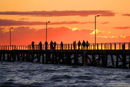People on Jetty watching Sunset.  Semaphore Beach, Adelaide, Australia.