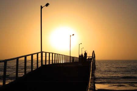 Orange Sunset behind People Walking along Largs Bay Jetty, Adelaide, Australia photo