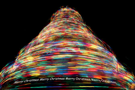 Merry Christmas - Long Exposure of Rotating Christmas Tree with Cycling Optical Fibre Lights against a black background photo
