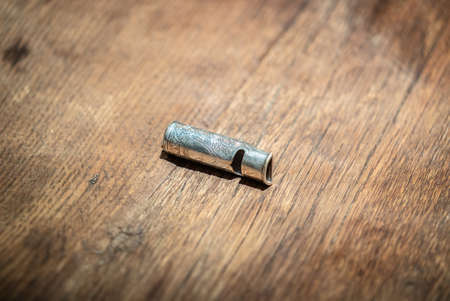 Silver metal dog whistle on wooden table