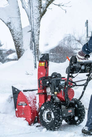A man cleans snow from sidewalks with snowblower in Bavaria Germany. 写真素材