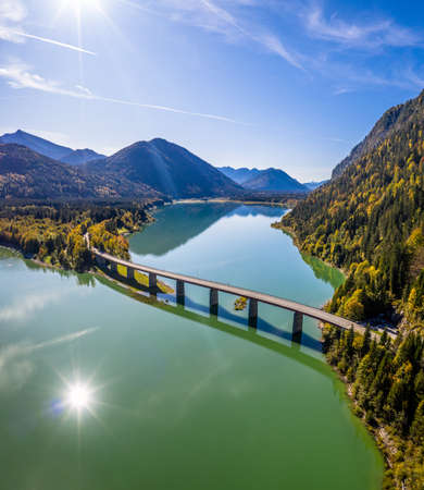 Scenic aerial view of the bridge over Lake Sylvenstein with beautiful reflections. Alps Karwendel Mountains in the back. Autumn scenery of Bavaria, Germany