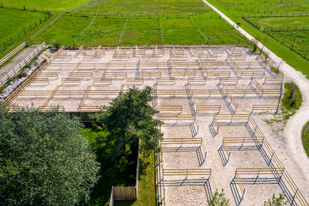 Outdoor boxes paddocks for horses on a farm. Wood fences. Aerial Drone Photo Banco de Imagens