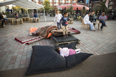 hanging around: Amsterdam, The Netherlands, 12 September 2014, at Westival, a free open air Cinema and culture festival on Mercatorplein. before the screening, preparation, people hanging around, children playing