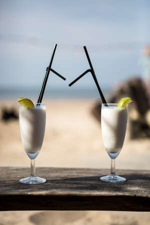 beach landscape: Cocktail glass with two straws and with beach landscape background Stock Photo