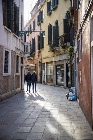 People walking in a narrow street in old town Venice, Italy Editorial