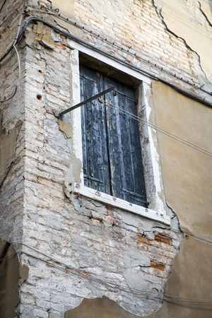 Decrepit brick wall with window with green painted wooden shutters photo
