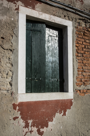 decrepit: Decrepit brick wall with window with green painted wooden shutter
