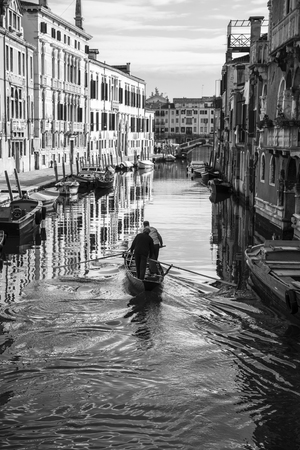 gondoliers: Typival venetian small canal or rio, Gondoliers training on the canals for the coming rowing race Vogalonga and Regata Storica, famous historical regatta. Travel and lifestyle