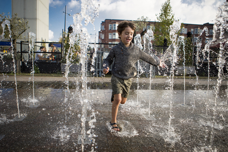 local festivals: Amsterdam, The Netherlands, 13 September 2014, at Westival, a free open air Cinema and culture festival on Mercatorplein, child having fun in the fountain Editorial
