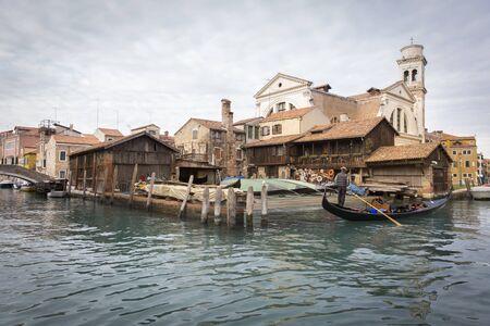 icone: gondolas outiside the water for renovation and maintenance, Gondola construction and repairs yard, Squero di San Trovaso and San Trovaso church, Venice Italy.
