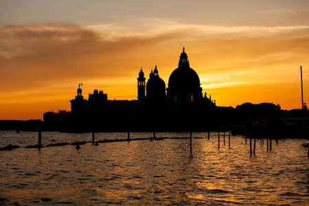 Romantic view of Punta della Dogana with Santa Maria della Salute Basilica in flamboyant sunset, Venise Italy photo