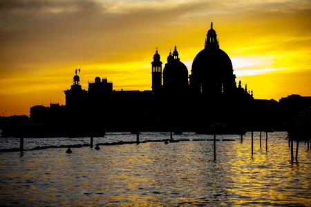 Romantic view of Punta della Dogana with Santa Maria della Salute Basilica in flamboyant sunset, Venice Italy photo