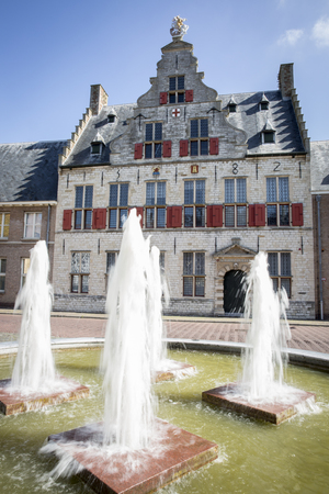Old medieval Dutch gable house with water jet fountain in front