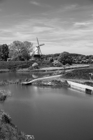 Typical Dutch landscape with a canal and a windmill