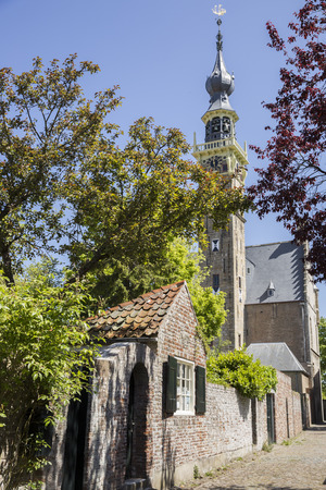 small cobble stone street with town halls gothic tower in the city of Veere, Zeeland province in the Netherlands