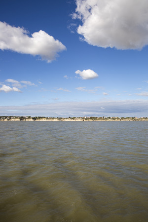 View of the coastline with seaside resort of Royan with blue sky and fluffy white cloud, France