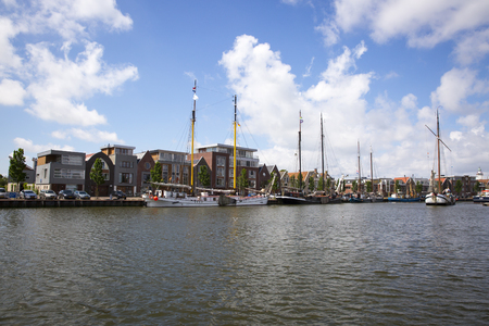 house gables: Noorderhaven canal with boats and houses in historic old town of Harlingen, Friesland, Netherlands Stock Photo