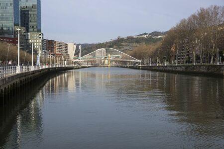 Bilbao, Spain - January, 29 2016: Nervion river with modern bridge Zubizuri designed by architect Santiago Calatrava. Zubizuri is Basque for white bridge, also called Campo Volantin Bridge or Puente del Campo Volantin. Editorial