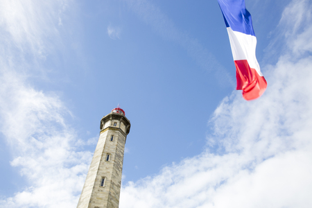 view from the ground of the 1854 Grand Phare des Baleines lighthouse with a French flag floating in front, Ile de Re, France. Stock Photo