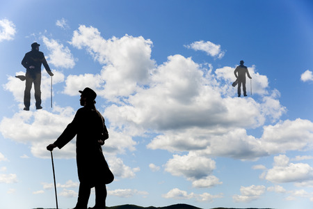 Surrealistic image of silhouettes of men with a cane and bowl hat climbing up the clouds in the sky Stock Photo