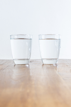 vineyard plain: 2 full glasses of clear healthy water standing on a wooden table Stock Photo