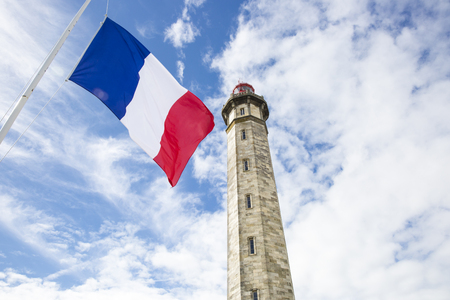 fraternity: view from the ground of the 1854 Grand Phare des Baleines lighthouse with a French flag floating in front, Ile de Re, France. Stock Photo
