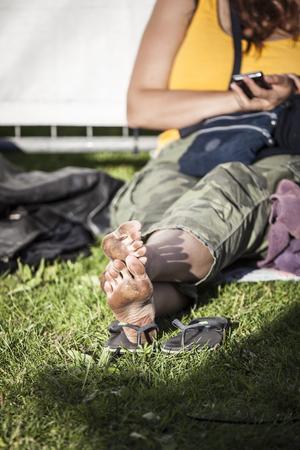 pieds sales: femme assise sur le sol avec gros plan sur ses pieds nus sales