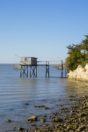 traditional fishermans wooden hut at the bottom of the limestone cliff in the estuary of Gironde, Talmont