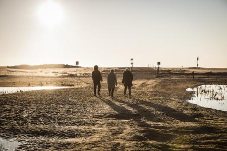 sur: Backlit silhouettes of people walking at sunset by the lagoon in natural reserve Casse de la Belle Henriette, lAiguillon sur Mer , Vendee, France