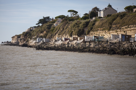fishing hut: traditional french fishermans wooden hut at the bottom of the limestone cliff in the estuary of Gironde, Meschers-sur-Gironde