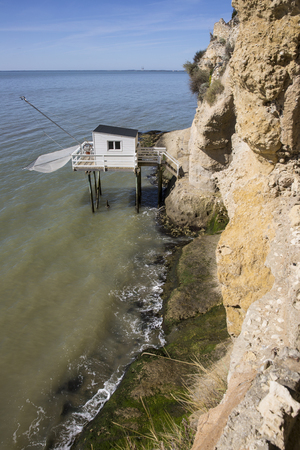 gironde: traditional fishermans wooden hut at the bottom of the limestone cliff in the estuary of Gironde, Meschers-sur-Gironde